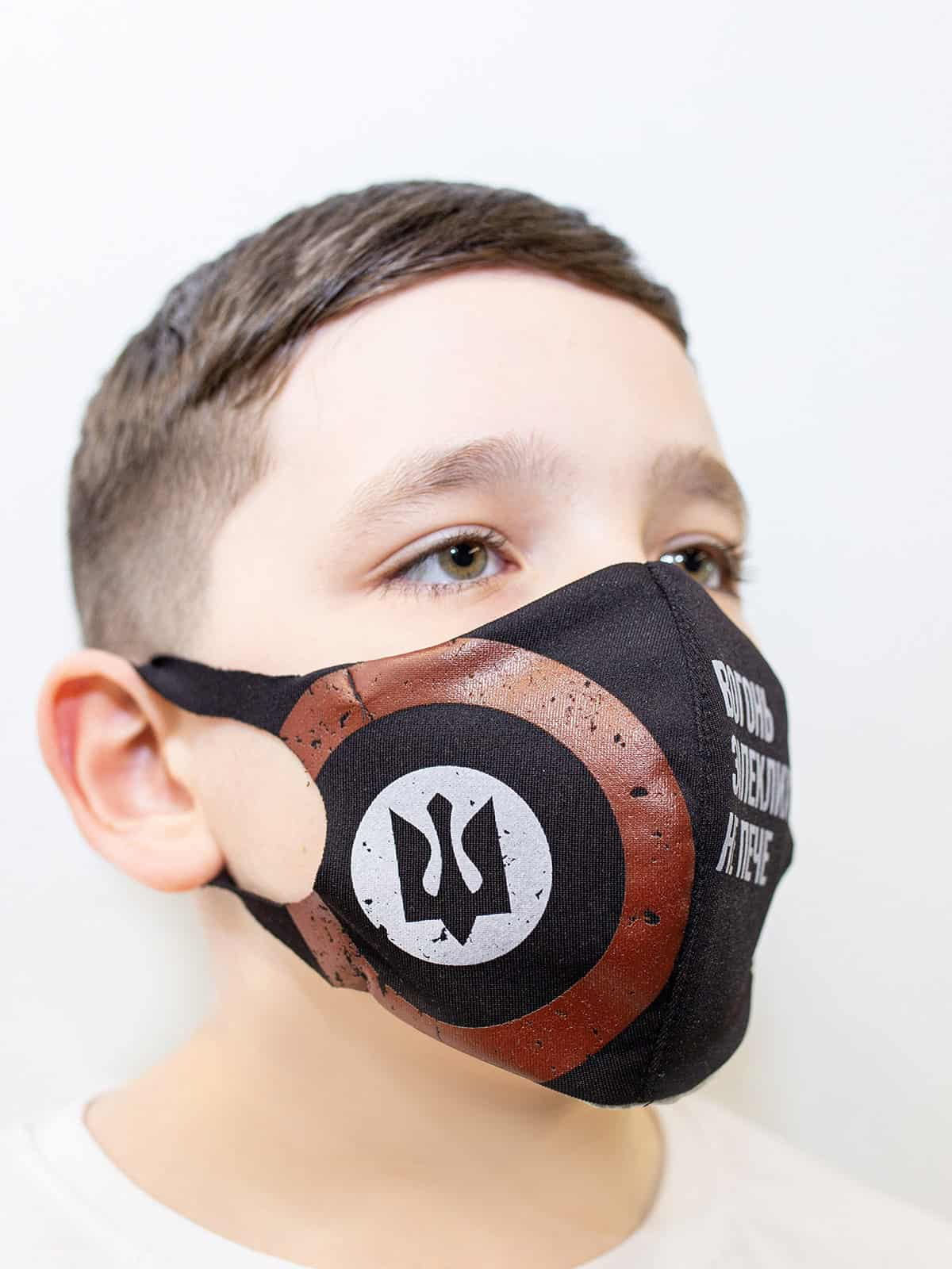 Kids Mask Trident. Color black. Reusable protective mask with a pocket for a replaceable filter Basic material (outer layer): scuba fabric (rayon 65%, lycra 5%, polyester 30%) – light-weight, elastic and smooth material that dries quickly and fits the face line effectively.